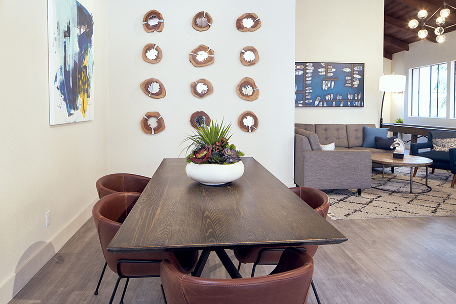 Lounge area with rectangular wood table, leather chairs, succulent plant, and wall art.