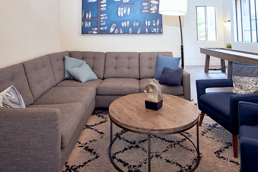 Lounge with rug, modern round table with horse sculpture, plush sectional couch, and comfortable chairs.