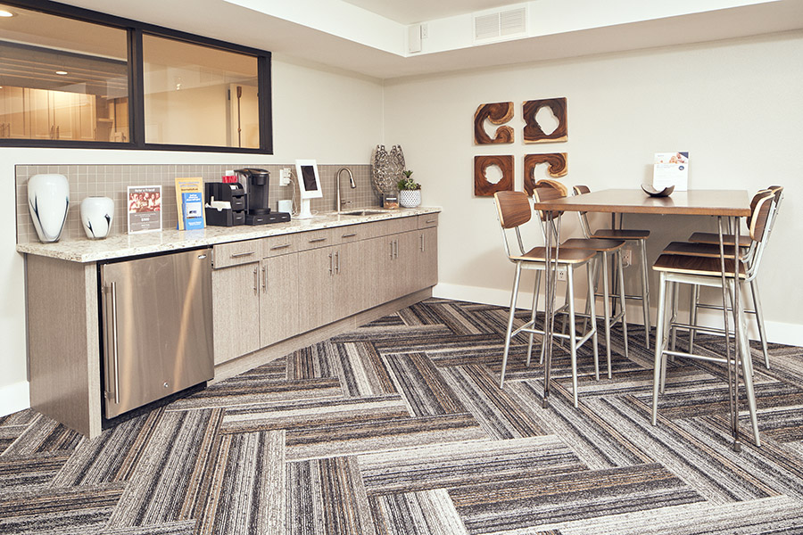Lounge with geometric carpet, small kitchen, tall table with modern stools, and wall art.