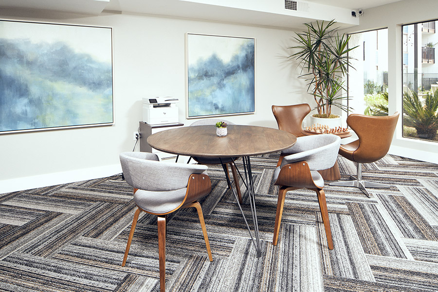 Lounge with geometric carpet, large wall art, and comfortable modern furniture.