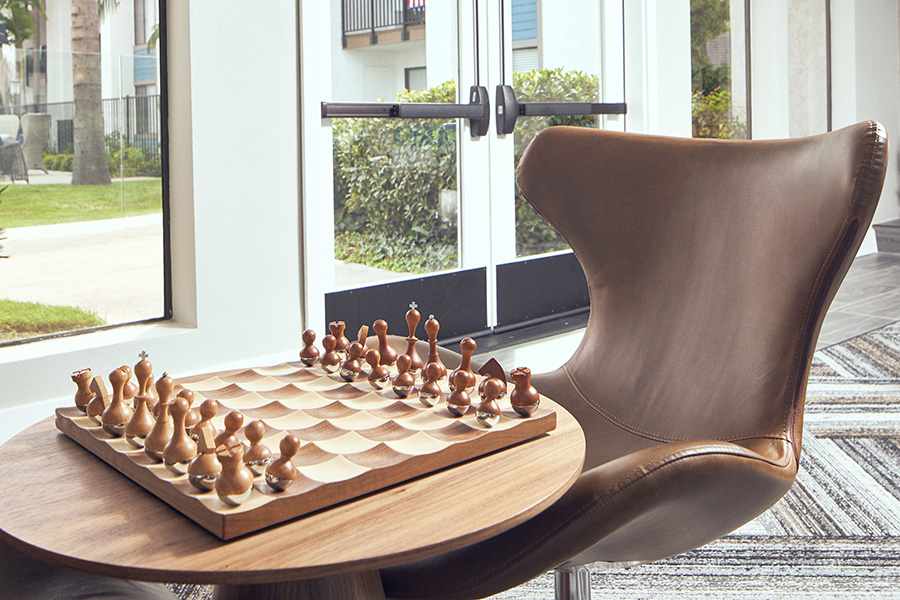 Detail of modern leather chair and wood table with scalloped chess set.