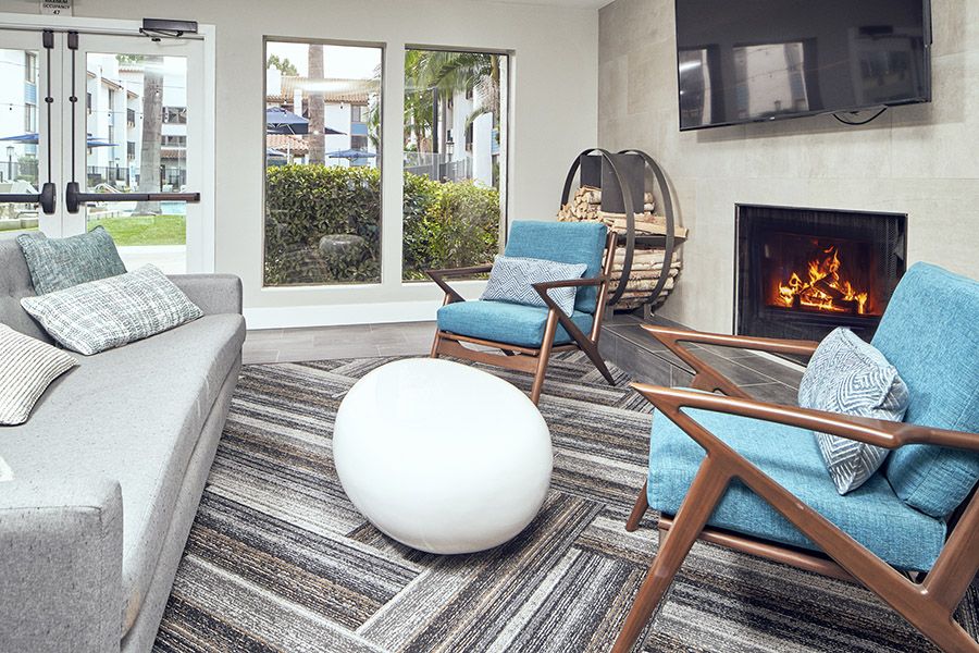 Lounge with geometric carpet, fireplace, wall mounted TV, and modern plush furniture.