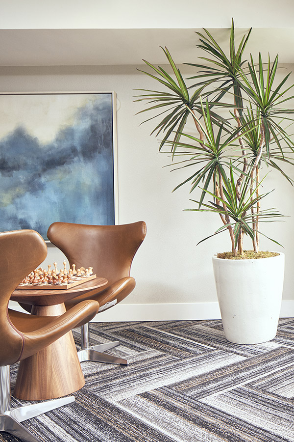 Lounge area with geometric carpet, large potted plant, wall art, and chairs with chess set.