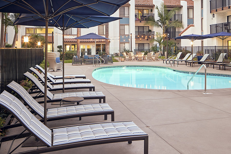 Pool area with plush lounge chairs, umbrellas, and string lights overlooked by apartment balconies.