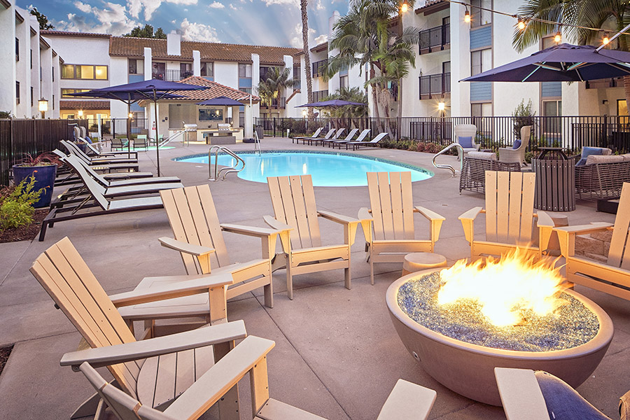 Pool area with fire pit, lounge chairs, and umbrellas overlooked by apartment balconies.
