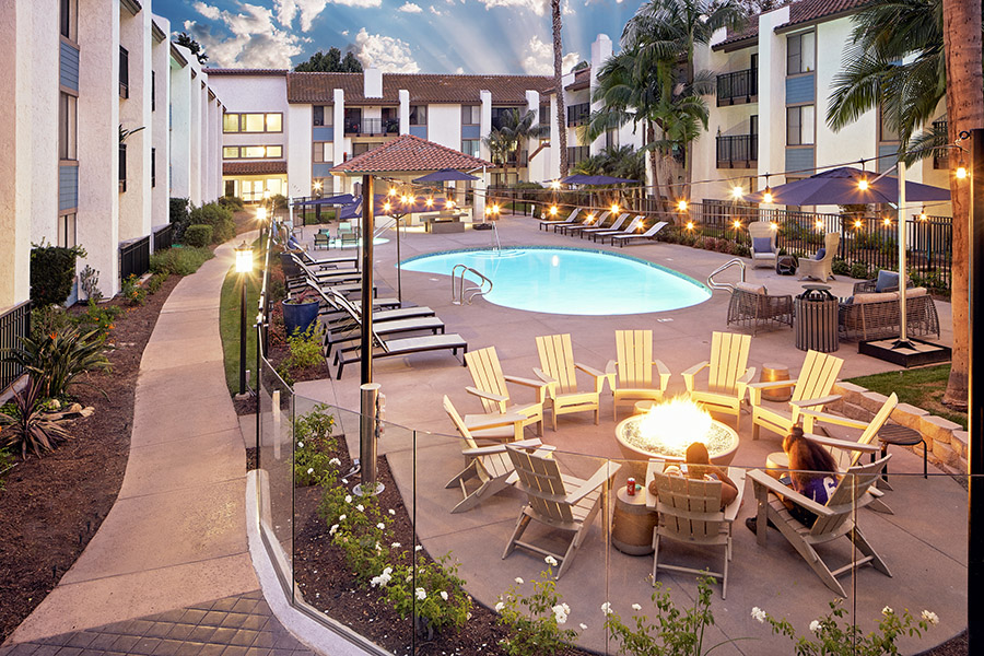 Pool area with fire pit, lounge chairs, umbrellas, and tall palm trees overlooked by apartment balconies.
