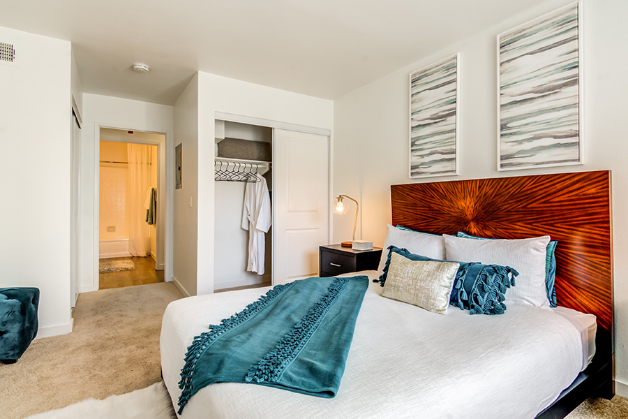 Bedroom with carpet floor, large platform bed with decorative headboard, and wall art.