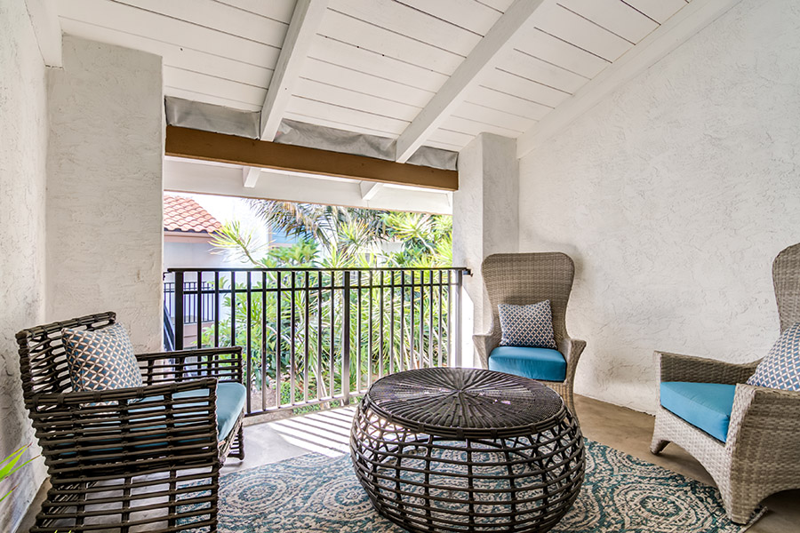 Apartment balcony with wicker furniture and large rug overlooking palm trees.