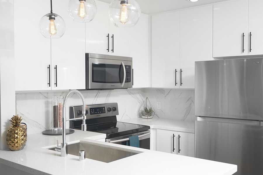 Apartment kitchen with white cabinets and counters, stainless steel appliances and sink, and retro pendant lights.
