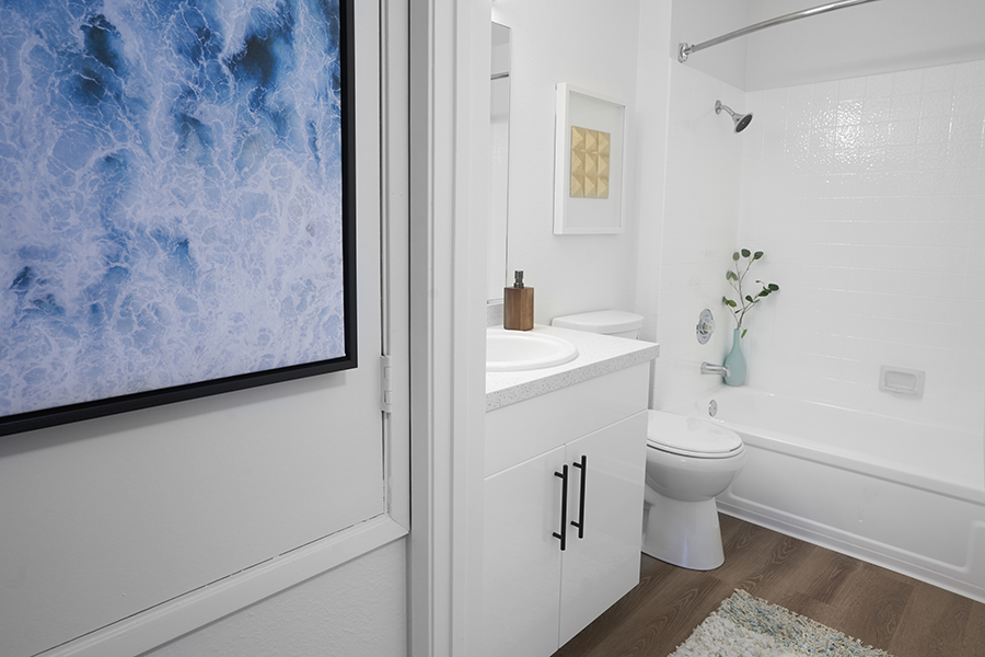 Bathroom with wood floor, white cabinets and counter, and tiled shower tub with curtain.