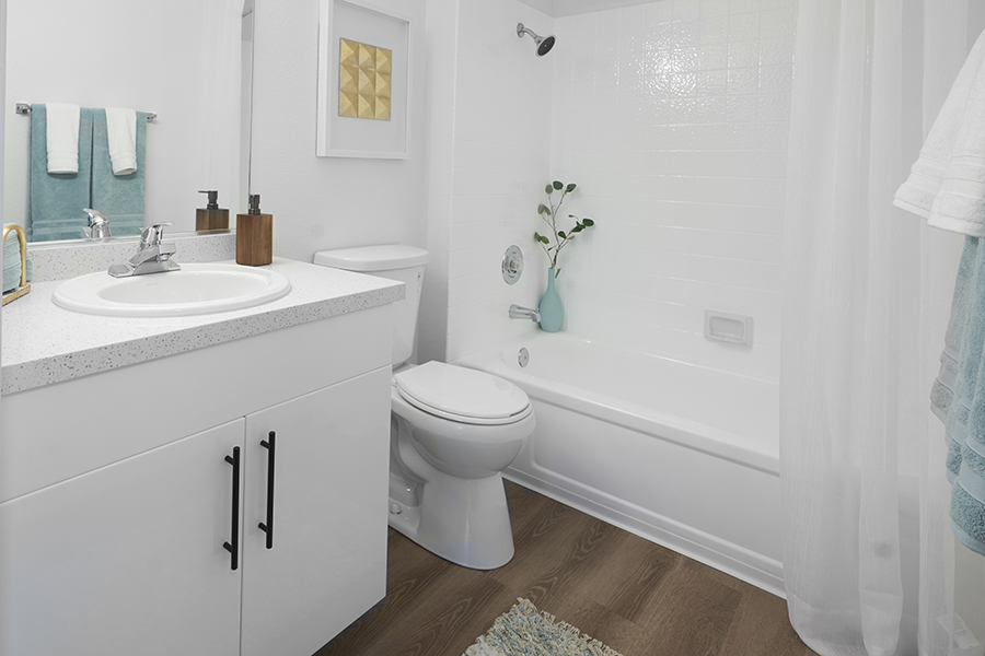 Bathroom with wood floor, white cabinets and counter, large mirror, and tiled shower tub with curtain.