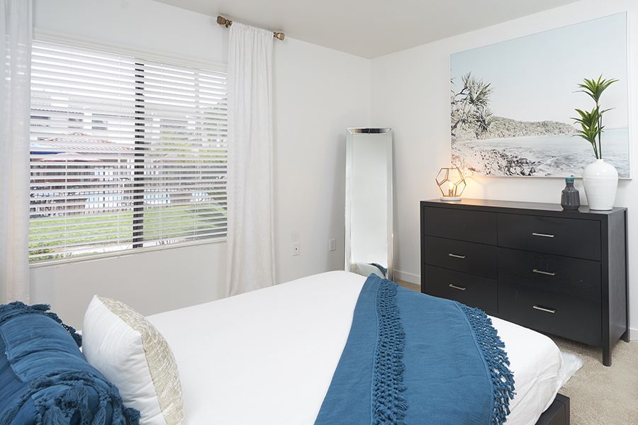 Bedroom with platform bed, dresser with plants and decor, large wall art, and full length mirror.