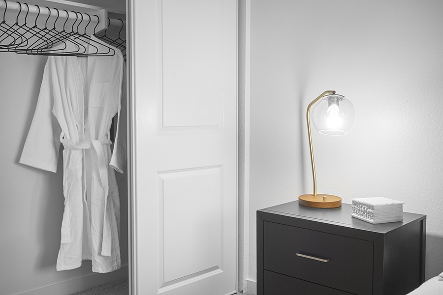 Bedroom with bedside table, brass lamp, and sliding closet door.