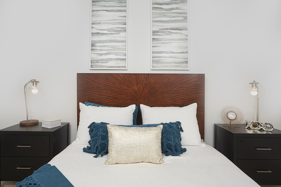 Bedroom with platform bed, plush bedding, bedside tables with brass lamps, and wall art.