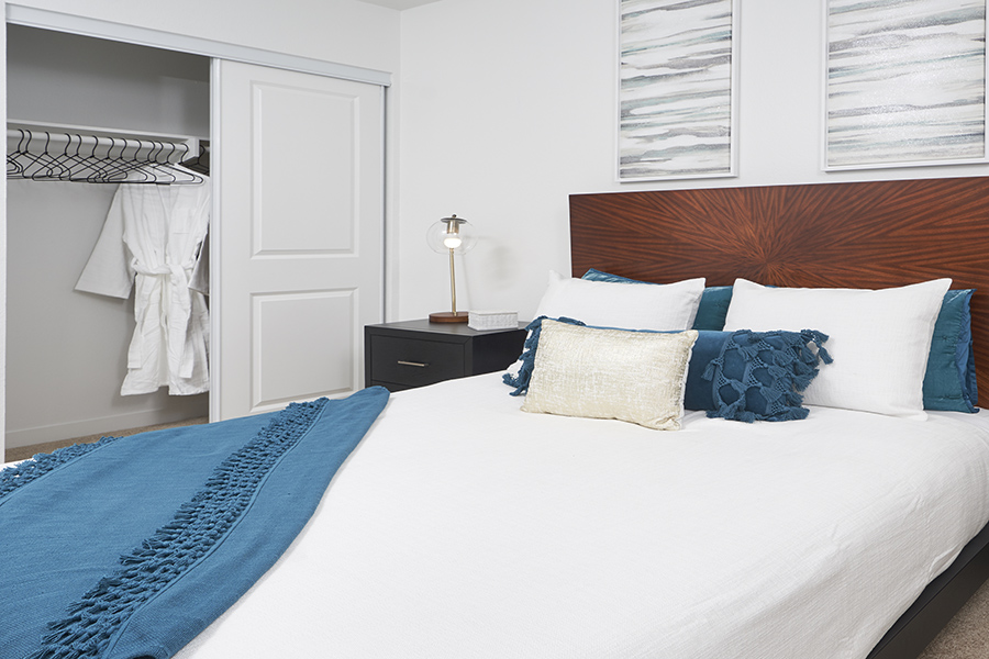 Bedroom with large platform bed, plush bedding, wall art, and sliding door to closet.