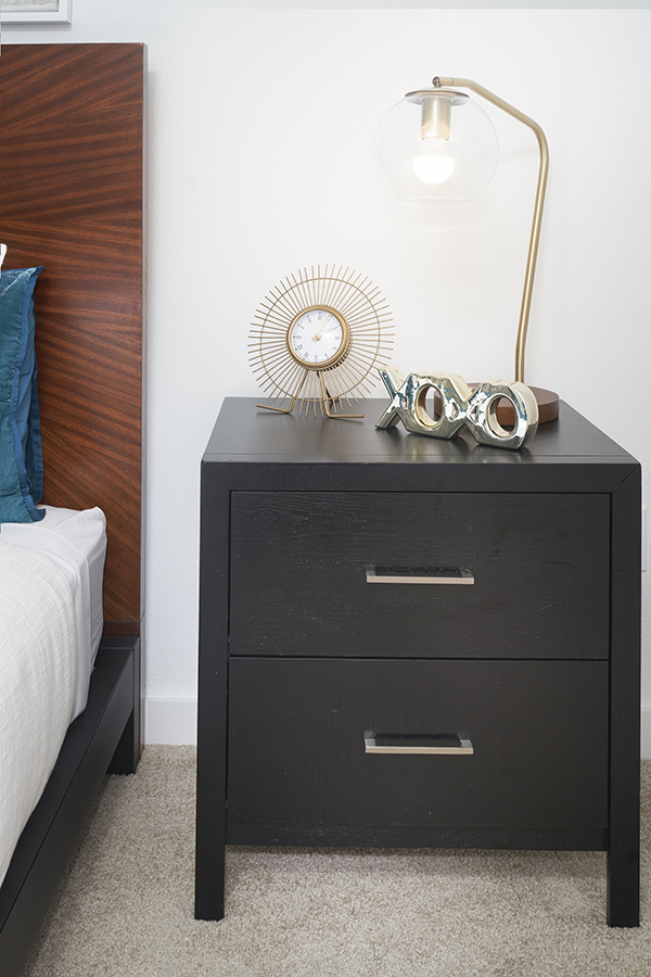 Bedside table with drawers, brass lamp and clock, and metal decor.