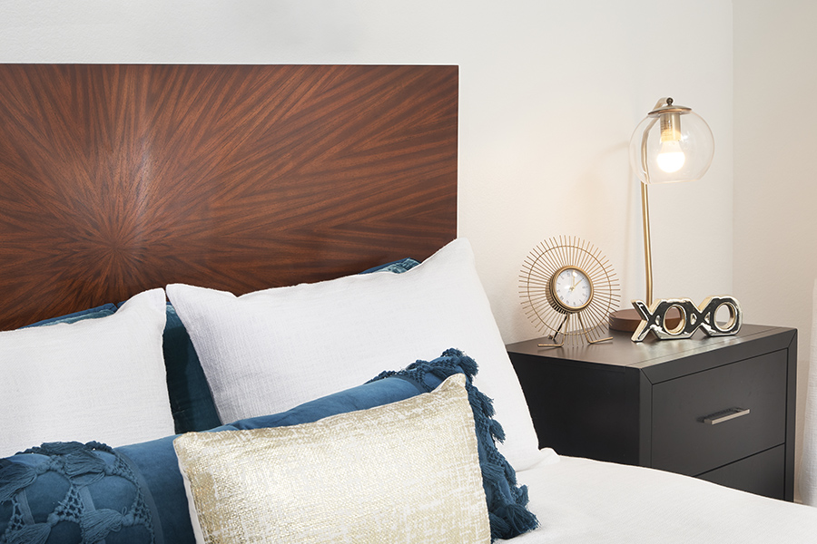 Detail of bed with wood headboard and plush bedding next to bedside table with clock and lamp.