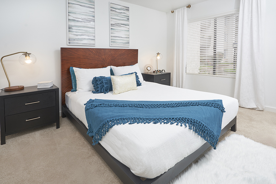 Bedroom with carpet floor, large platform bed with headboard, and side tables with brass lamps.