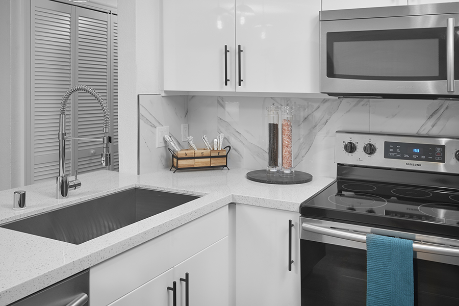 Kitchen with white cabinets and counters, stainless steel sink, and large salt and pepper mills.