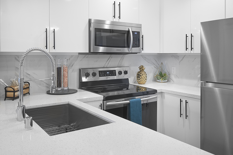 Kitchen with white cabinets and counters, stainless steel appliances and sink, and decor.