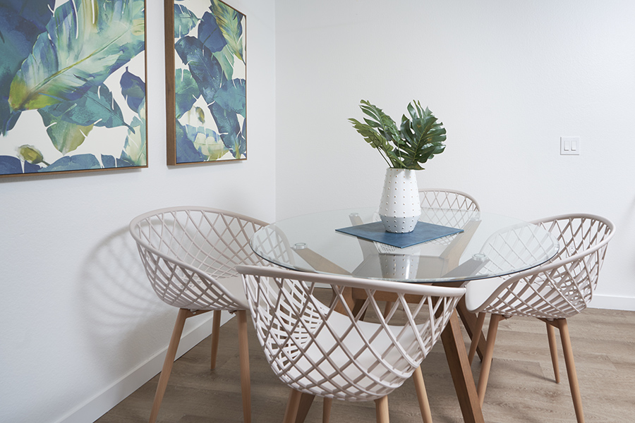 Detail of wood and glass dining table with geometric chairs and potted plant.