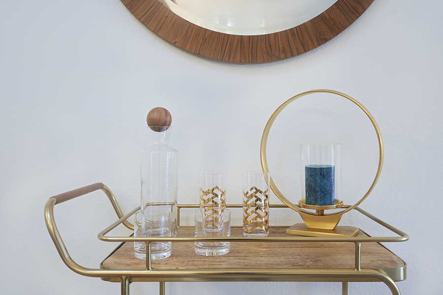 Detail of brass and wood bar cart with glasses, decanter, and decorative candle holder.