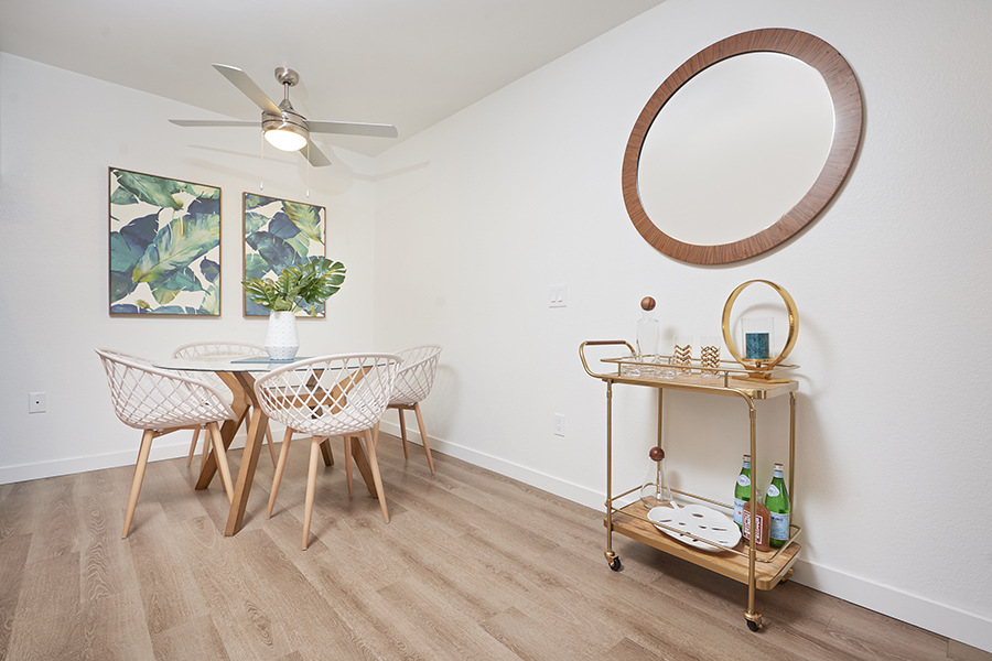 Dining area with wood floor, modern wood and glass dining table, bar cart, and large wall art.