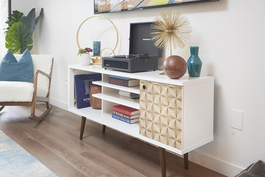 Mid century media console with decor, books, artwork, and folding record player.