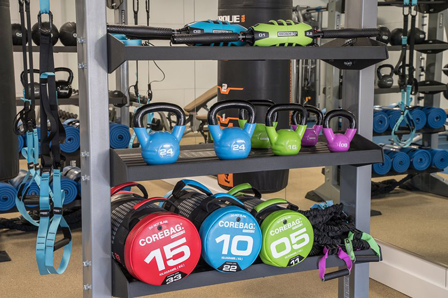 Fitness center shelves with kettlebells, sand bags, and resistance bands.