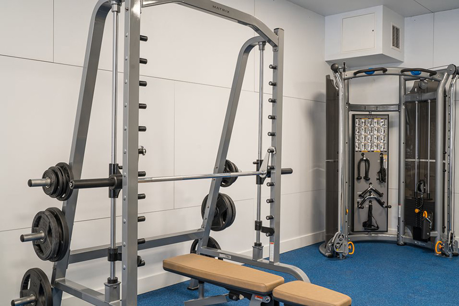 Fitness center with carpet floor and weight lifting equipment.