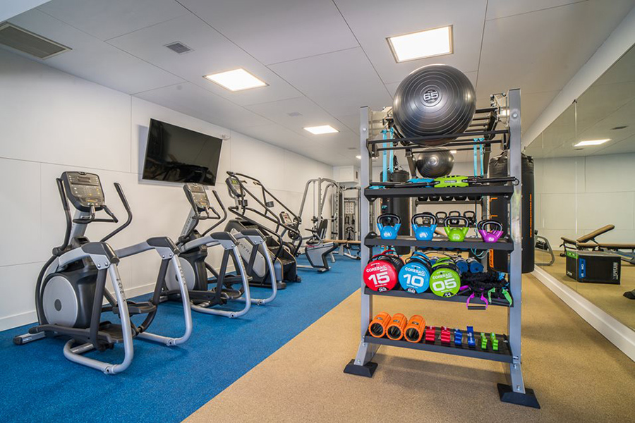 Fitness center with wall mounted TV and mirrors, rows of cardio machines, and shelves of calisthenics equipment.