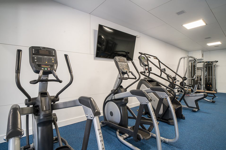 Fitness center with wall mounted TV and rows of cardio and weight lifting equipment.