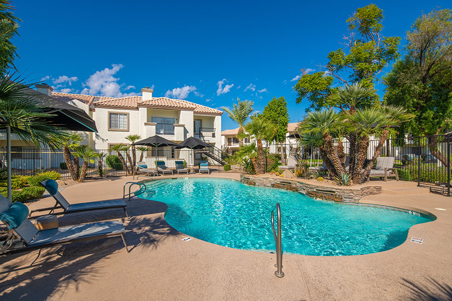 Pool area with bright blue water, paved patio, comfortable lounge chairs, and tall palm trees.
